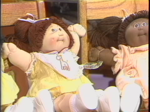 stockvideo's en b-roll-footage met cabbage patch kids dolls on display there is a closeup shot of two cabbage patched kid dolls in yellow dresses. one doll is black and one doll is... - pop speelgoed