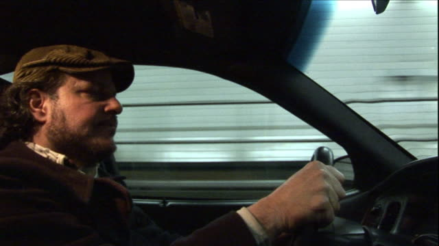 a cabbie steers his taxi through a lighted tunnel. - lenkrad stock-videos und b-roll-filmmaterial