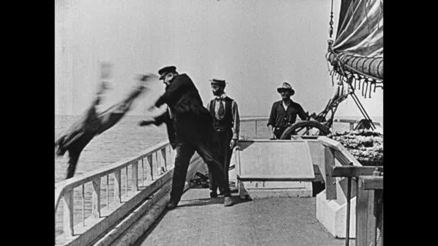 1923 cabin boy spills coffee on ship captain's (joe roberts) hand and gets thrown overboard - 消しゴム点の映像素材/bロール