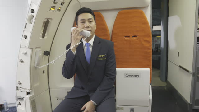 cabin crew or air hostess working in airplane . flight attendant  cabin crew pick up interphone and make  call in flight. - crew stock videos & royalty-free footage