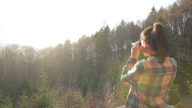 Cabine Retreat-Jeune femme regardant avec une vue jumelles.
