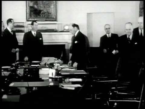 Cabinet members around table Pres Harry S Truman entering everybody raising shaking hands taking seat VS Truman talking White House