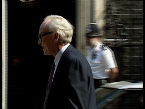 ; c)5.40pm england: london: 10 downing st: kenneth baker out car and in nicholas ridley out car and in, poses and waves on doorstep city: trade... - 内閣改造点の映像素材/bロール
