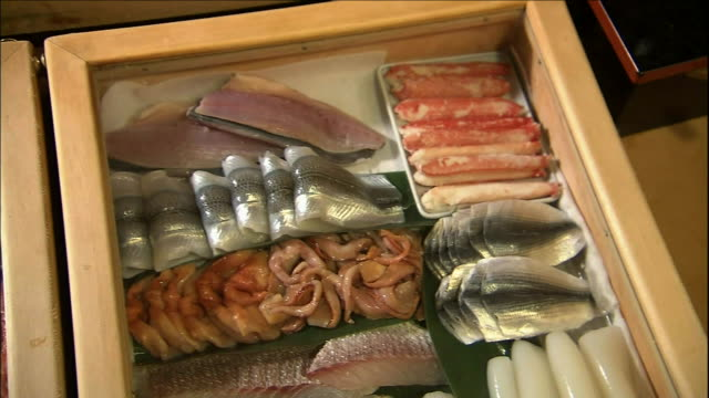 cabinets in a sushi shop display assortments of sushi. - nigiri stock videos and b-roll footage