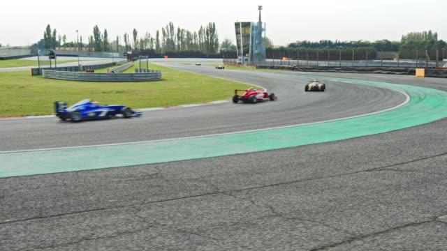 vídeos de stock, filmes e b-roll de ts cable cam: formula cars speeding around the turn on the race track - perícia