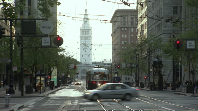 MS ZI Cable car and street traffic with clock tower in background, San Francisco, California, USA