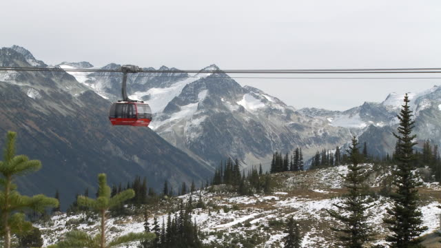 WS ZO Cable car crossing frame in front of rocky mountain / Whistler, British Columbia, Canada