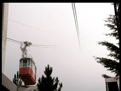 Cable car disappears into thick cloud as it travels up mountainside Picos De Europa Spain