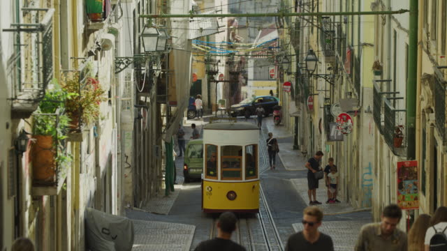 cable car driving on steep hill in city / lisbon, lisboa, portugal - tram stock videos & royalty-free footage