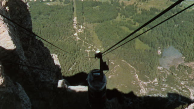 A 1959 cable car gondola lift moves through the mountainsides of the  Dolomites in the Italian Alps of  Italy.