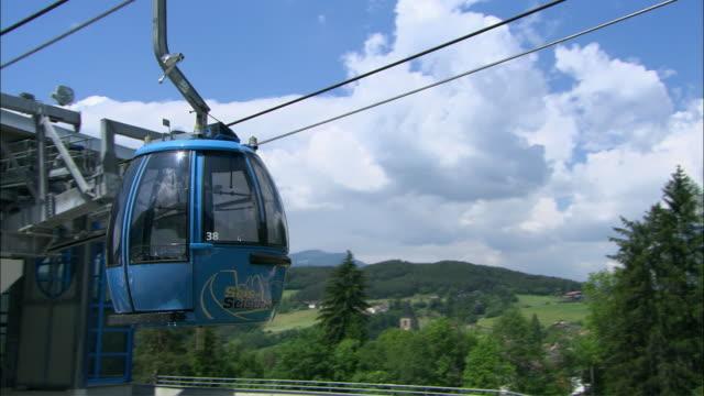 vídeos de stock e filmes b-roll de ws pan cable car leaving station and heading away toward mountain, vipiteno, bolzano-bozen, italy - cable