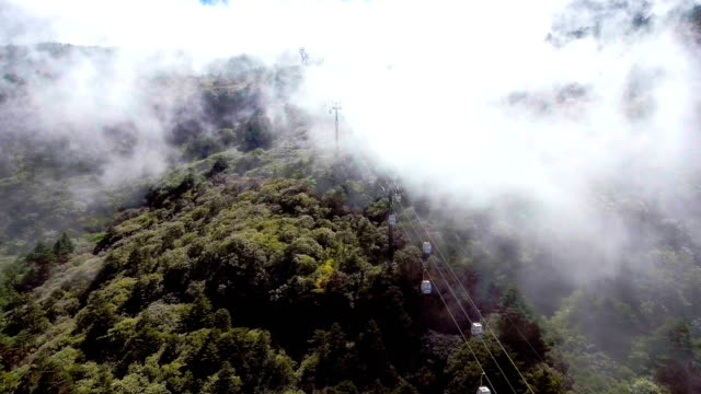 vídeos de stock e filmes b-roll de cable car running on the mountains with fog flowing, jiaozi mountaions, yunnan province, china - encosta