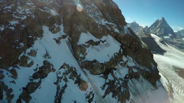cable car travelling down from klein matterhorn snow covered mountain over glaciers, swiss alps - inquadratura dalla sciovia video stock e b–roll