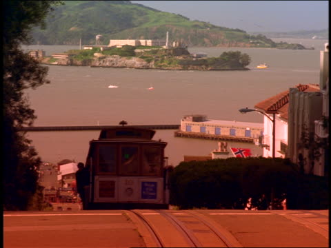 cable car with passengers riding up steep hill / alcatraz island in background / san francisco, ca - north beach san francisco stock videos and b-roll footage