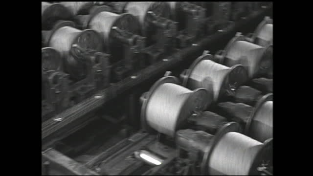 cable passing through machinery; worker operating overhead crane lifting cables and dipping them into acid bath; spools of cable being reeled and... - 1940 1949 bildbanksvideor och videomaterial från bakom kulisserna