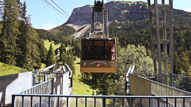 ms cable way leaving to bring people on top of seceda cliff on italian dolomites / selva di val gardena, italy - val gardena video stock e b–roll