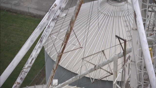 vidéos et rushes de cables and beams extend from silos at a factory. - silo