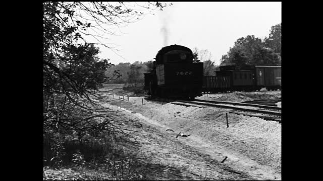 "caboose labelled ""new york central"" pulling away from camera; close up on train wheels on track; various views of smoking train on tracks in the... - 1940 1949 video stock e b–roll"