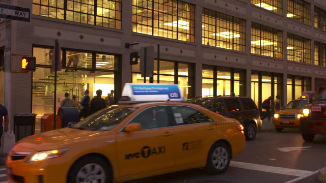 cabs and a nyc tow truck pass in front of the apple store in chelsea early evening - apple store stock videos & royalty-free footage