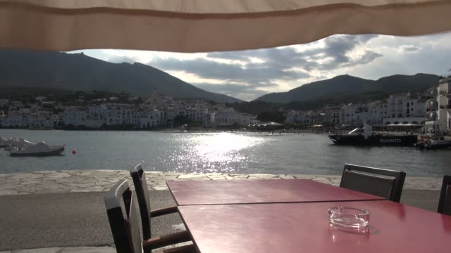 Cadaques In Catalonia Taken from seat in bar across table on which there's an ashtray In the background moored yachts and sailing boats Cars and...