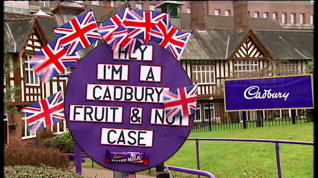 stockvideo's en b-roll-footage met cadbury taken over by kraft lorry along to factory entrance / staff along inside / staff outside bourneville place protestor dressed as john bull... - kraft