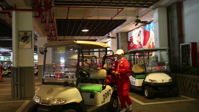 A caddy drives a golf cart at Mission Hills Golf Club in Dongguan China on Saturday Dec 21 Caddies prepare golf carts in garage area Caddies prepare...