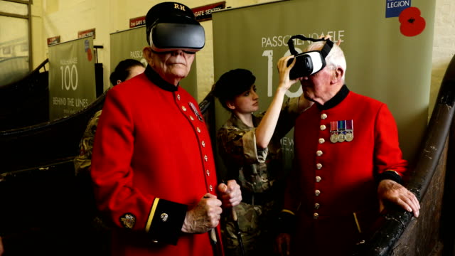 cadet maisie jackson adjusts a virtual reality headset for chelsea pensioners bill 'spud' hunt and chelsea pensioner john kidman during the royal... - cyberspace stock videos & royalty-free footage