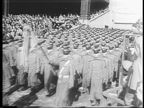 cadets from west point march onto the field of yankee stadium, stand at attention / stadium stands filled with people / newreel cameras in stands. - 1943 stock-videos und b-roll-filmmaterial
