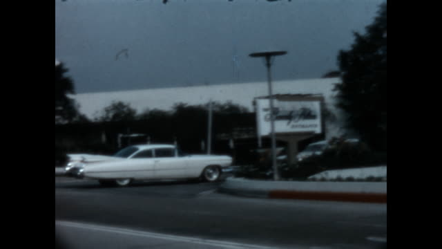 stockvideo's en b-roll-footage met a cadillac coupe de ville turns into the beverly hilton hotel in the 1960's - beverly hilton hotel
