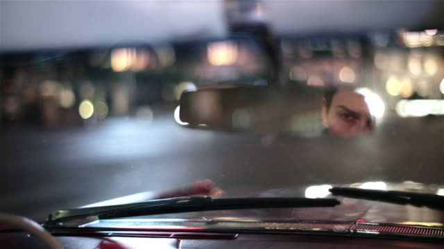 Cadillac driver slicks hair back in rearview mirror