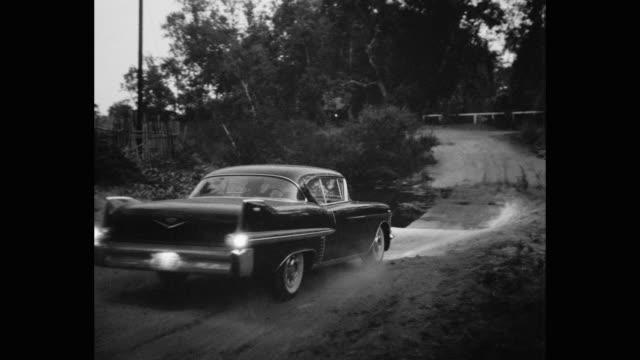 vídeos de stock, filmes e b-roll de 1957 cadillac driving on dirt road passing through forest at dusk - escrita ocidental