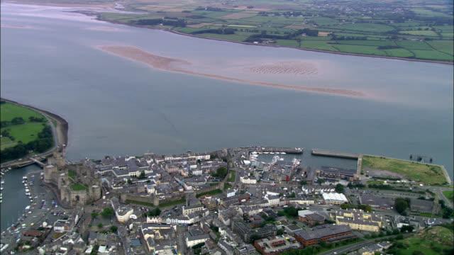caernarfon castle  - aerial view - wales, caernarfonshire and merionethshire, united kingdom - wales stock videos & royalty-free footage