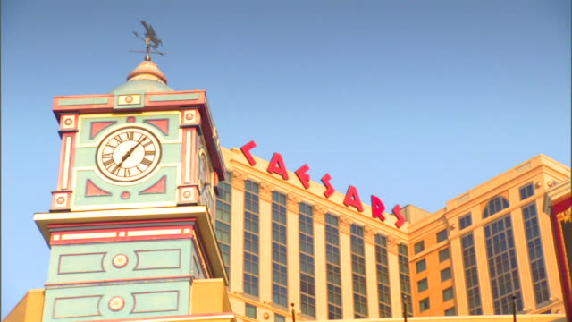 caesars lettering on building at roofline behind bally's wild west hotel casino clock tower td/tu ballys entrance themed casinos early american west... - boardwalk stock videos & royalty-free footage