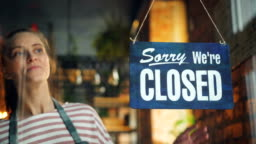 Cafe manager changing closed to open sign on window smiling looking outside