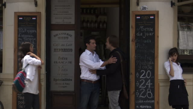 MS cafe owner stepping out onto street to greet man and woman/ Man and woman entering cafe as owner motions server talking on cell phone to enter with him/ Buenos Aires, Argentina