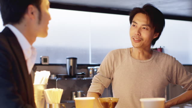ms a cafe owner talks and laughs with a customer / tokyo, japan - customer focused stock videos & royalty-free footage