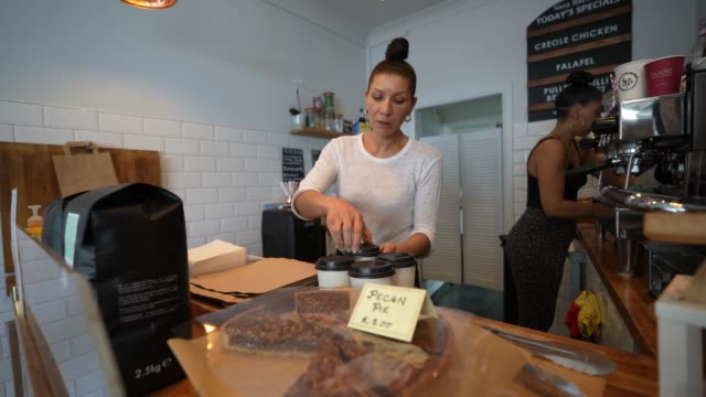 cafe owner wendy birch behind the counter servicing customers at her business, sista barista, a black female family run coffee shop near waterloo... - business stock videos & royalty-free footage