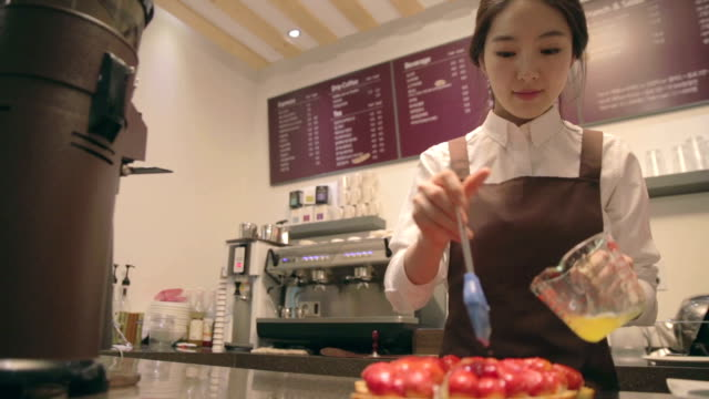 Cafe staff brushing syrup on strawberries on pie