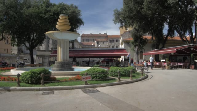 cafes and water fountain in dante square in old town, pula, istria county, croatia, adriatic, europe - bench stock videos & royalty-free footage
