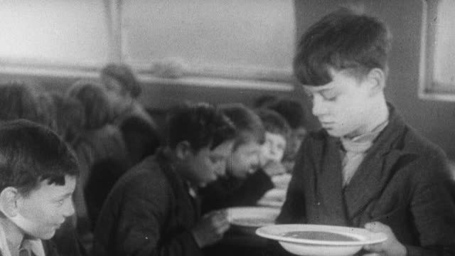 1939 montage cafeteria worker serving hot soup to students who are seated and eating lunch / united kingdom - canteen stock videos & royalty-free footage