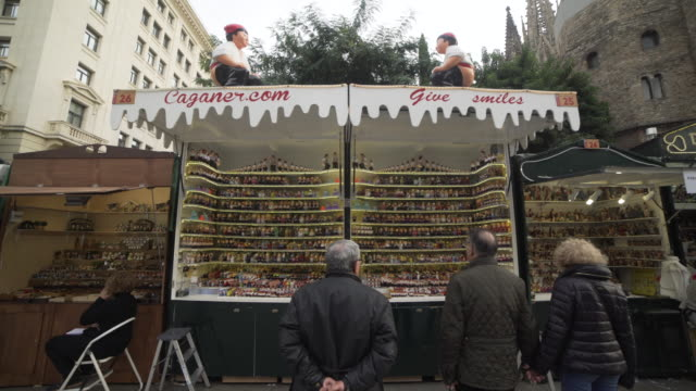 caganers figurine stall at barcelona christmas market - catalogna video stock e b–roll