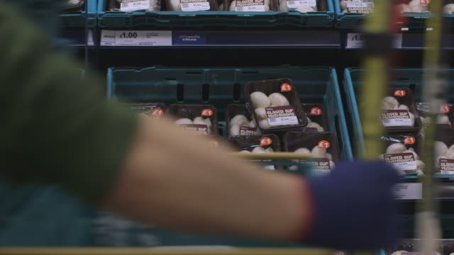 A cage on wheels is pulled passed mushrooms in a supermarket aisle, UK.