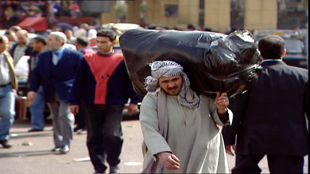 cairo scenes mcu on an egyptian man carrying a heavy load on his shoulder on a busy street in cairo - door to door salesperson stock videos & royalty-free footage