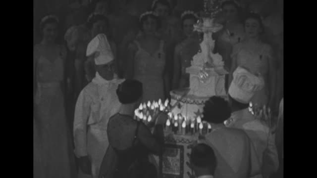 cake is wheeled out onto dance floor at coronation ball at albert hall / debutantes take their places / princess marina duchess of kent cuts the cake... - 舞踏会点の映像素材/bロール