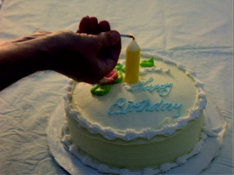 vídeos de stock, filmes e b-roll de cake with one candle reads happy birthday on white tablecloth hand tries to light candle with lit match birthday cake on january 01 1960 in los... - toalha de mesa