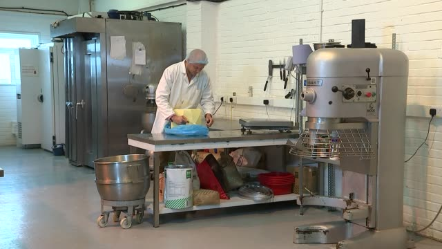 cakes being made at raise bakery in worthing; large block of butter / lumps of butter being cut from block and placed in mixing bowl / butter in... - worthing点の映像素材/bロール