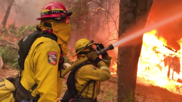 vidéos et rushes de cal fire firefighter sprays water on a home next to a burning home as the camp fire moves through the area on november 9, 2018 in magalia, california. - californie