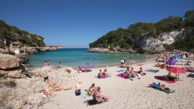 cala llombards (llombards beach) with people at the beach. - lying down stock videos & royalty-free footage