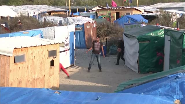 Amber Rudd to meet French counterpart T04051616 / TX Men playing football next to makeshift huts
