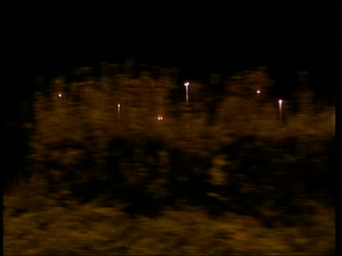 calais ext at night group of asylum seekers hiding faces as make way along to channel tunnel order ref t31080103 - calais stock videos and b-roll footage